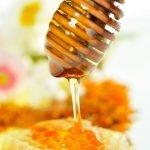 Nahaufnahme von Honigwabe mit Honiglöffel