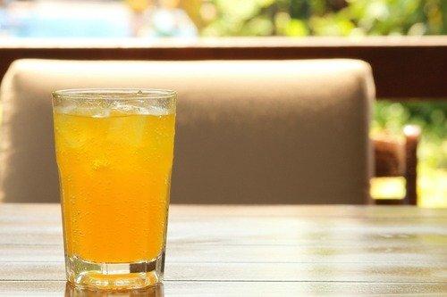 Ein Glas gefüllt mit kohlensäurehaltigem Kombucha stehen auf einem Tisch