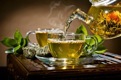 Glasteekanne gießt Tee in zwei Glastassen stehend auf einem Tisch ein